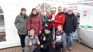 Caritasdirektor Wolfgang Langer mit dem Pokal (Bildmitte) im Kreis der Caritasmitarbeitenden