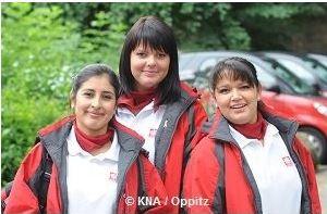 Drei junge Frauen in Caritas-Kleidung.