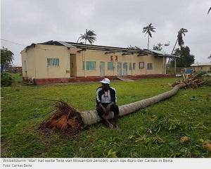 Ein Mann sitzt vor einem abgedeckten Haus auf einer umgestürzten Palme.