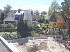 Ein Bild der Baustelle in der Sonne - die ersten Bäumchen sind gepflanzt.