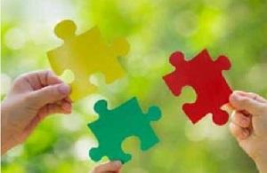 Drei Hände fügen drei farbige Puzzleteile zusammen.