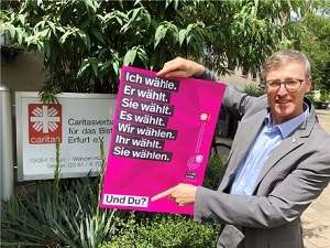 Diözesan-Caritasdirektor Wolfgang Langer mit einem der Plakate zur Wahlkampagne 2019.