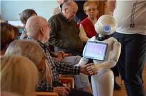 Der kleine Pflegeroboter reicht einem Bewohner die Hand.