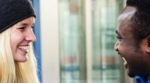 Eine Frau im fröhlichen Gespräch mit einem Mann mit Migrationshintergrund.