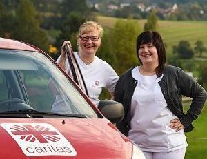 Zwei Caritas-Mitarbeitende vor einem roten Caritas-Auto.