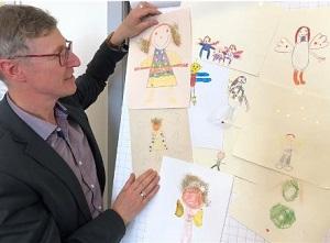 Caritasdirektor Wolfgang Langer neben den selbst gemalten Bildern der Kinder.