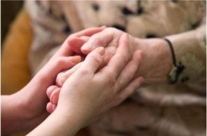 Hände eines älteren Menschen werden von denen einer jungen Frau umfasst.